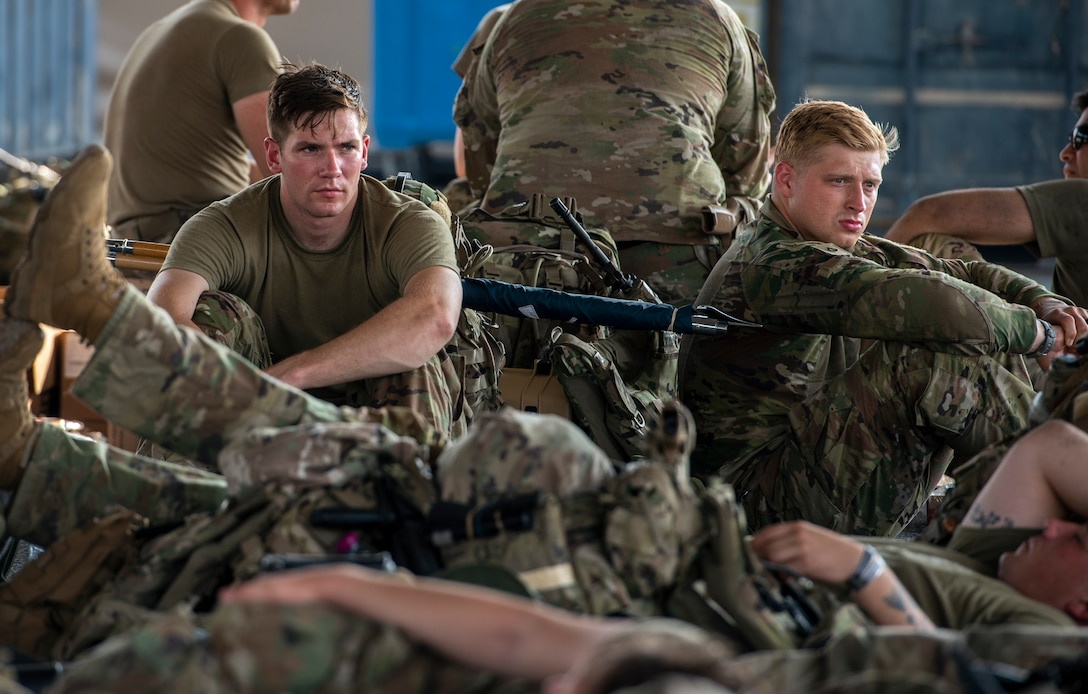 Service members rest and wait at Personnel Support for Contingency Operations on their way to Afghanistan Aug. 18, 2021, at an undisclosed location in Southwest Asia.