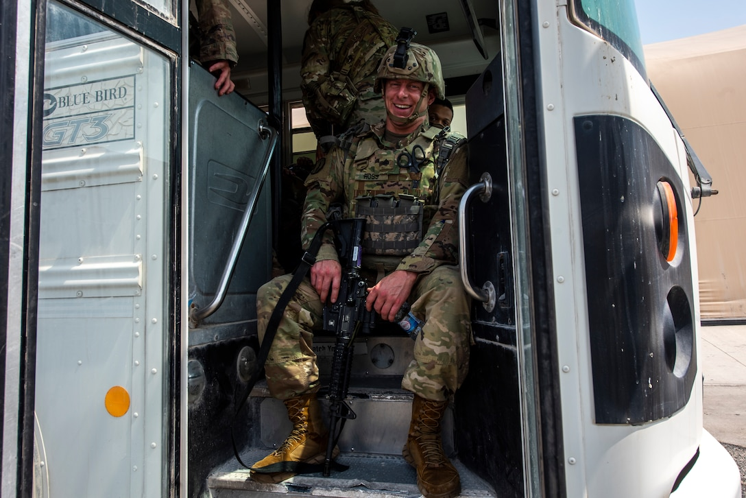 A service member waits on a bus prior to deploying to Afghanistan Aug. 19, 2021, at Al Udeid Air Base, Qatar.