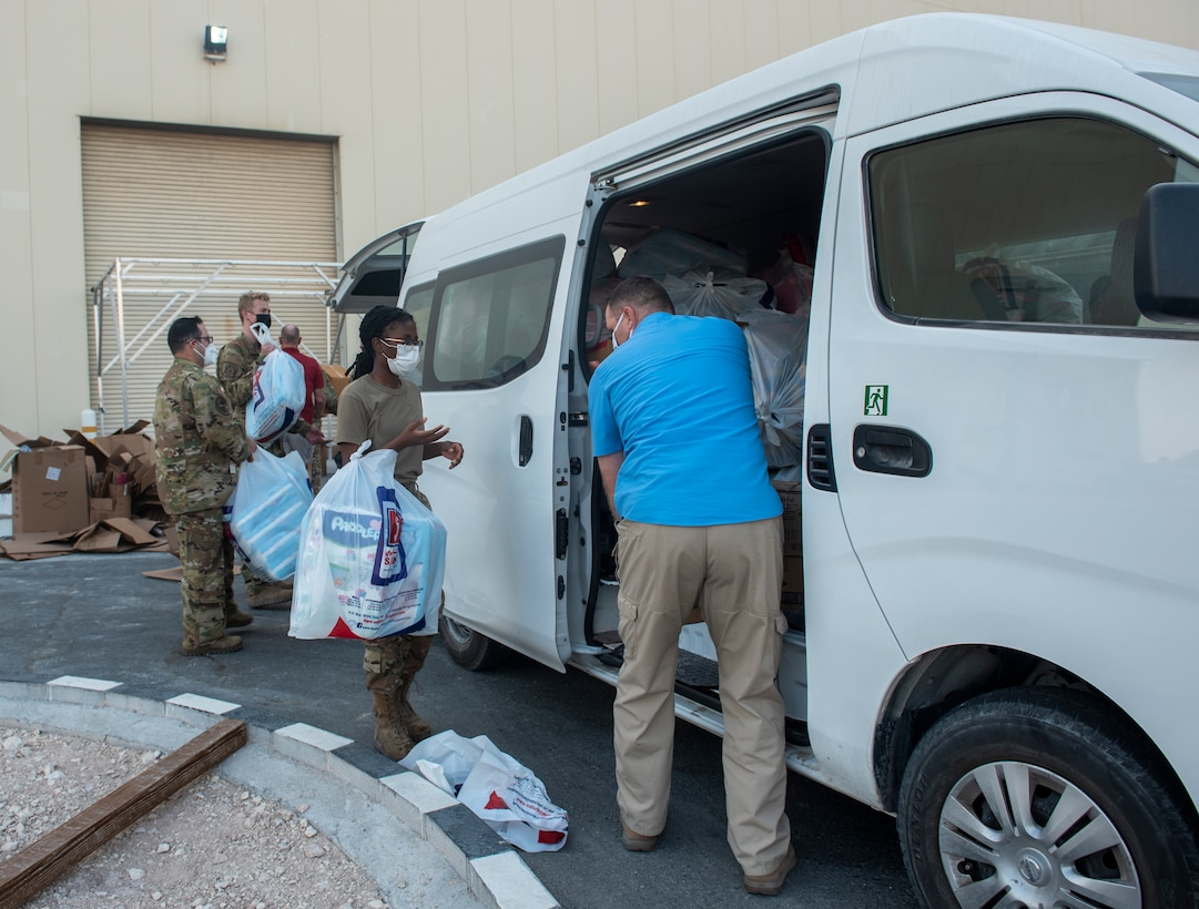 Members from the 379th Air Expeditionary Wing carry donations for Afghanistan evacuees into a hangar in the CENTCOM area of responsibility, Aug. 19, 2021.