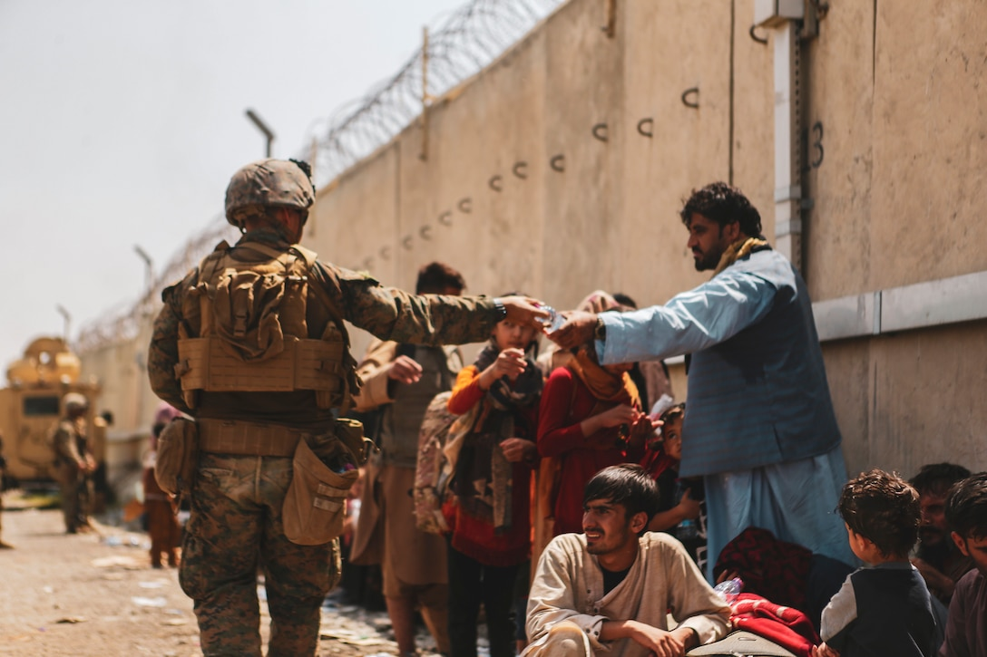A Marine hands a bottle of water to a man standing amidst a group of people.