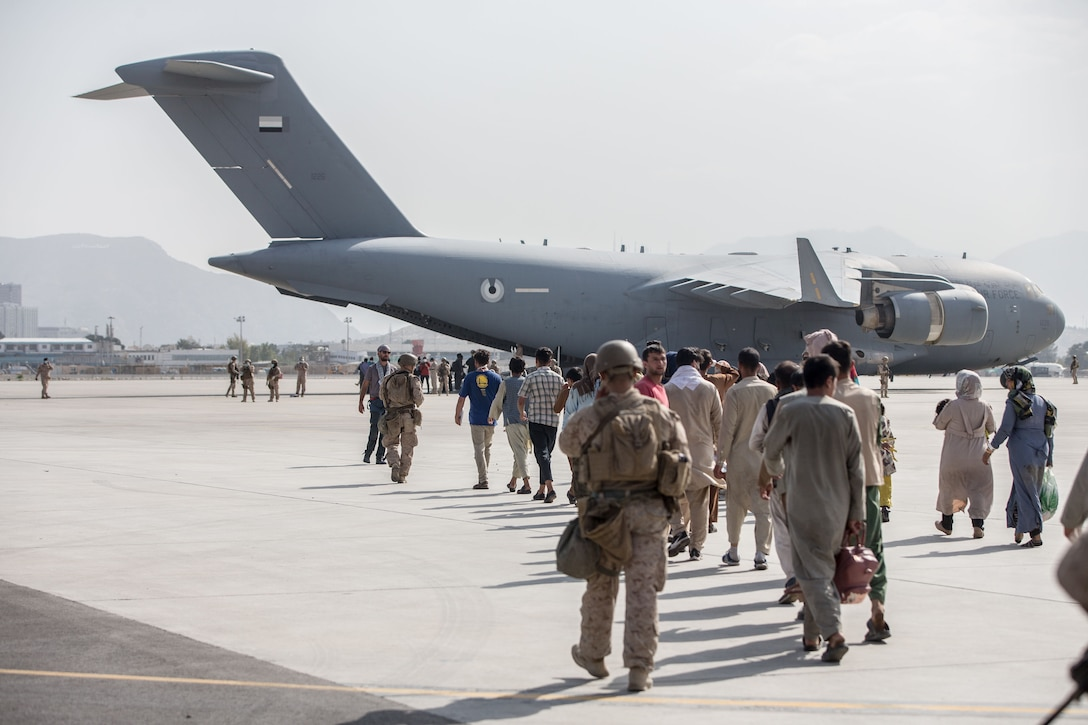 A Marine escorts a group of people walking toward an aircraft.