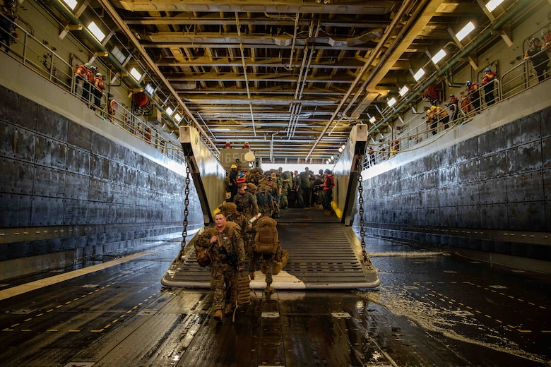 Marines assigned to 1st Battalion, 6th Marine Regiment, Bravo Company, disembark a landing craft, utility, in the well deck of the San Antonio-class amphibious transport dock ship USS Arlington (LPD 24), Aug. 18, 2021. Arlington is deployed to U.S. Naval Forces Southern Command/U.S. 4th Fleet to support humanitarian assistance and disaster relief efforts in Haiti following a 7.2-magnitude earthquake Aug. 14, 2021.