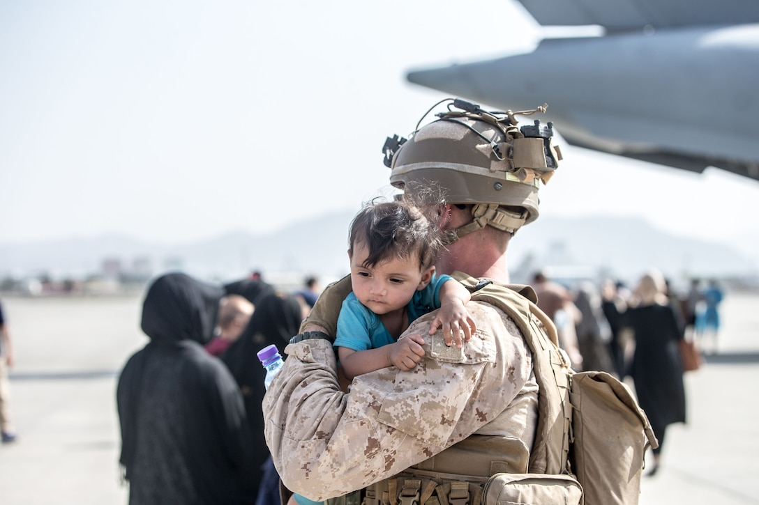 A Marine holds an infant on his shoulder while others line up to board an aircraft.