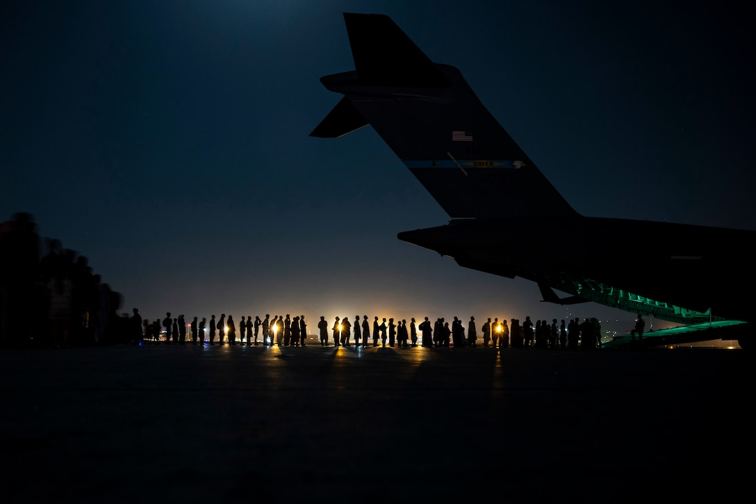 A line of people board an aircraft at night.