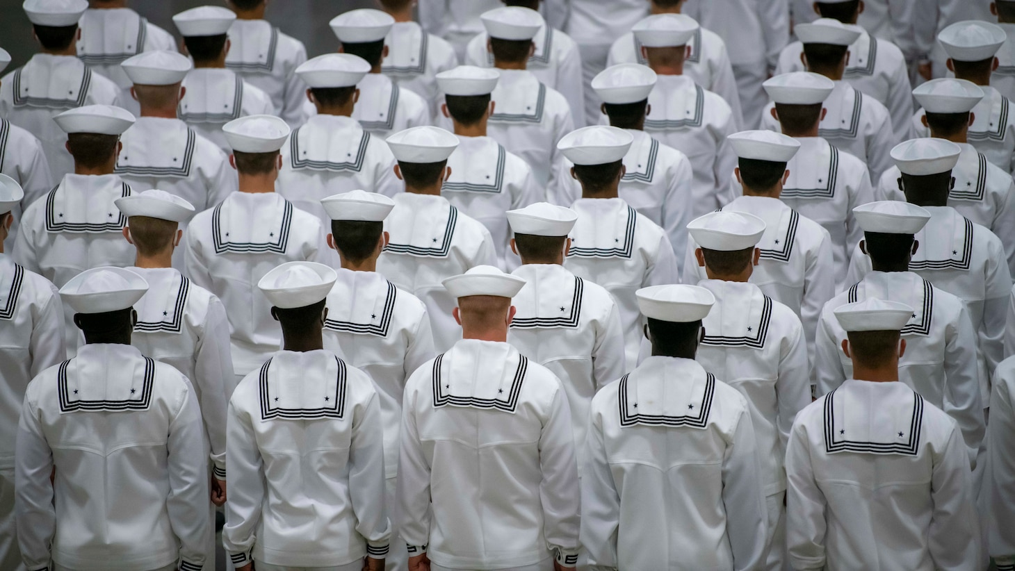 Sailors graduating from boot camp stand in formation after entering Midway Ceremonial Drill Hall during a pass-in-review graduation ceremony at Recruit Training Command.