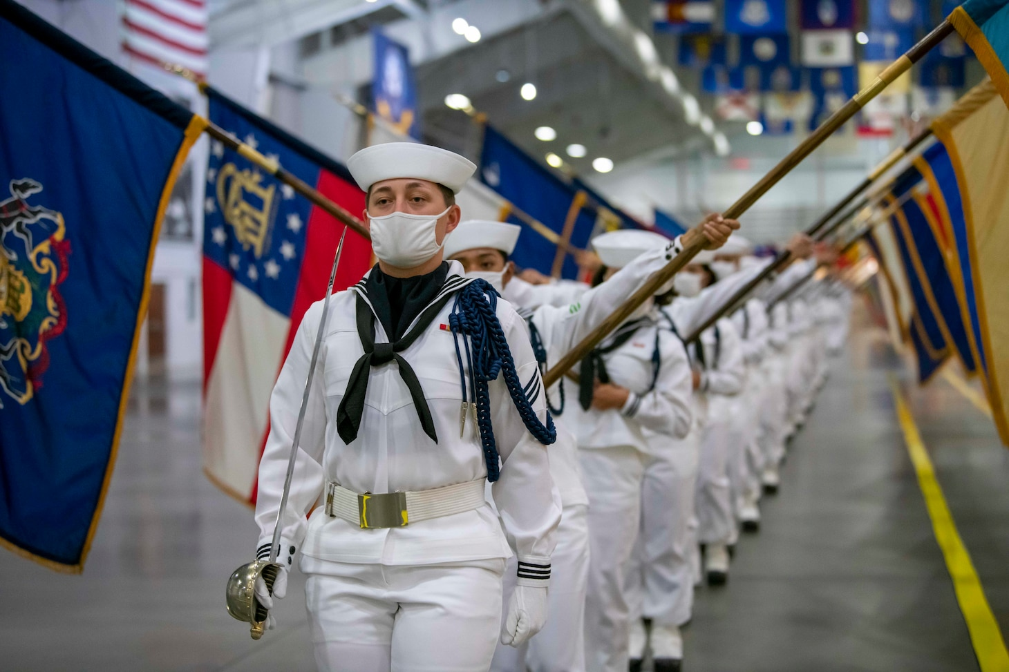 Performance division recruits carrying state flags march on the drill deck.