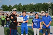 U.S. Marine Staff Sgt. Zachary Quade, left, a recruiter with Recruiting Station Cleveland presents the scholar athlete award to Wade Urick who attends Defiance High School and has a 4.02 Grade Point Average during the first Great American Rivalry Series (GARS) of the year at Defiance High School, Defiance, Ohio, Aug. 19, 2021. Leading up to the GARS game Marine recruiters attended Defiance's football practice, pep rally and lunch break. (U.S. Marine Corps photo by Cpl. Nello Miele)