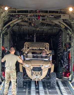 U.S. Air Force Senior Master Sgt. Nathan Sole, left, 109th Airlift Squadron provides directions to Tech. Sgt. Ross Wehrle, 133rd Contingency Response Flight, Minnesota Air National Guard, right, as he backs the light tactical all-terrain vehicle (MZRZ) onto a C-130 Hercules from the Minnesota Air National Guard in St. Croix, Virgin Islands, Aug. 17, 2021.