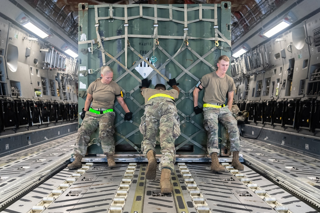 Three airmen push  a large load of supplies on an aircraft.
