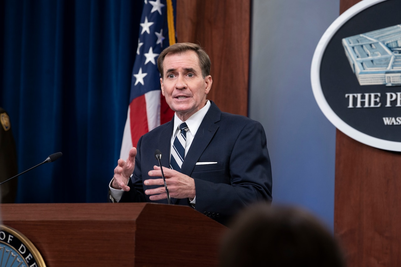 A man dressed in a business suit stands at a lectern.
