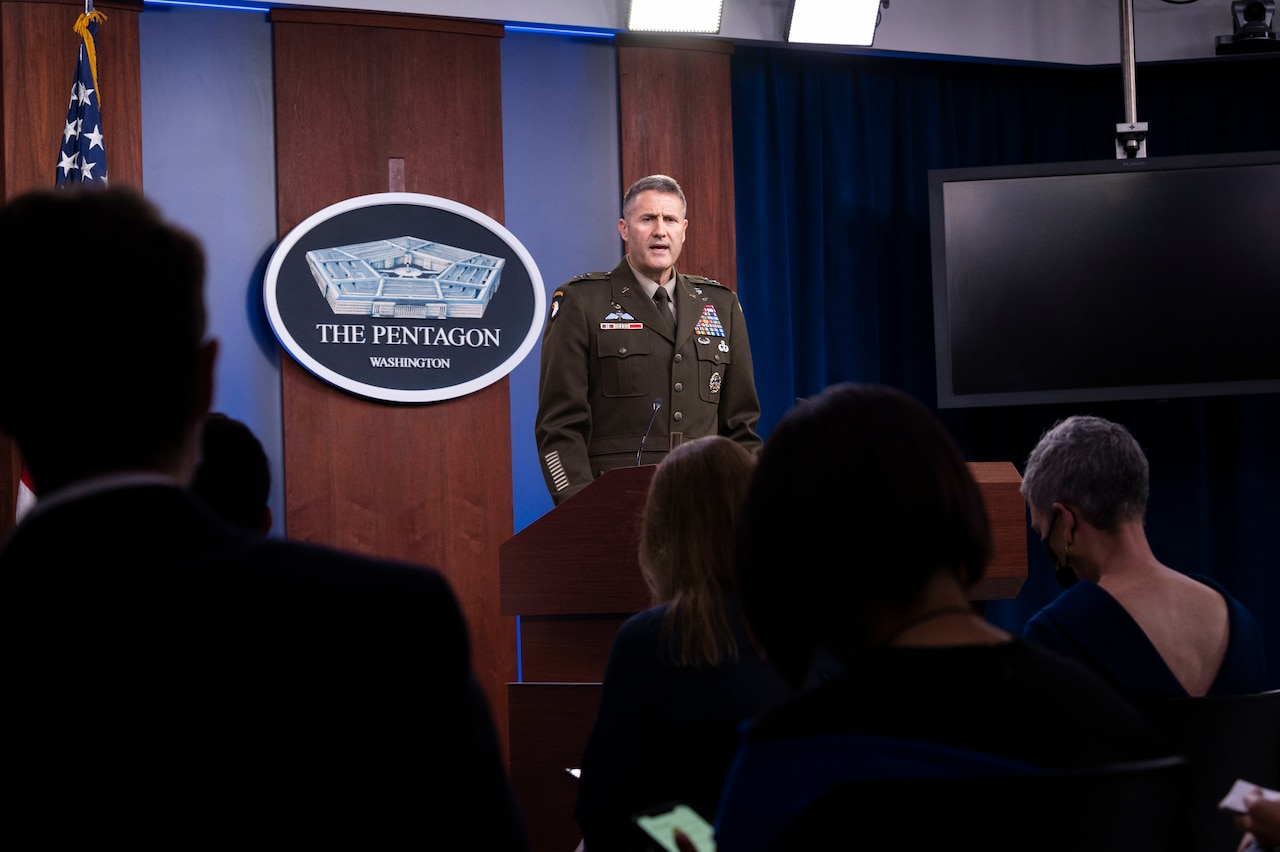 A man dressed in a military uniform faces an audience. The sign in the background indicates that he is at the Pentagon.