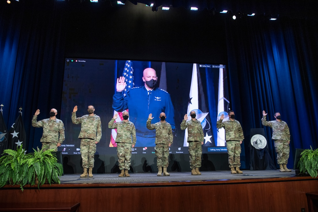 Military members raise their hands to reaffirm their oath to the Space Force