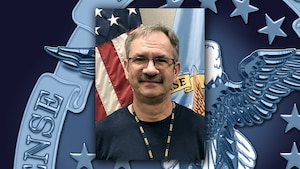 Head and shoulders image of white guy wearing glasses in front of the US and  DLA flags.