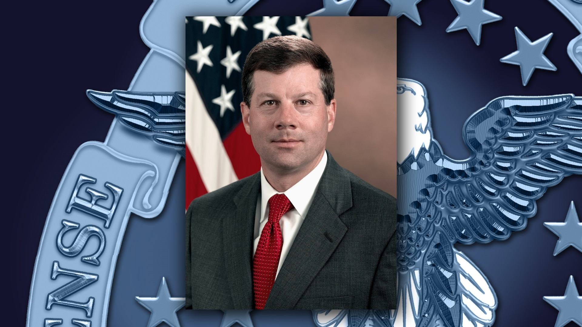 White man in a black suit and red tie sits in front of the US flag.