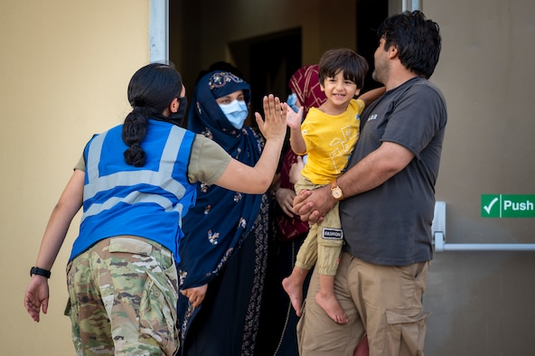 A U.S. service member high-fives a child who was evacuated from Afghanistan Aug. 21, 2021, in an undisclosed location somewhere in Southwest Asia.