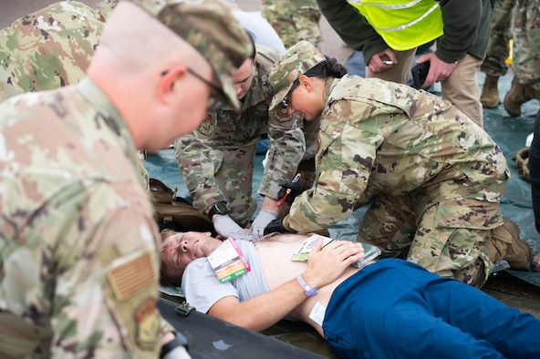 Airman 1st Class Michael Butterfill, center, 341st Civil Engineer Squadron horizontal construction technician, simulates being injured during an exercise Aug. 20, 2021, at Malmstrom Air Force Base, Mont.
