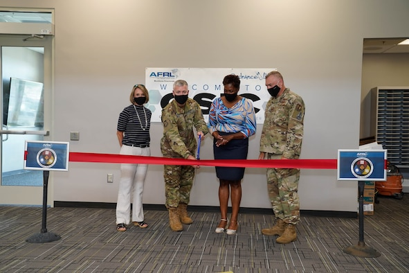 AFRL Munitions Directorate Commander, Col. W. Tony Meeks cuts the ceremonial ribbon for the new Ordnance Science Innovation Center on Eglin AFB, Fla. He is flanked on the left by Integration and Operations Division Chief, Jaime Pinto, and to the right by Ordnance Division Chief, Segrid Harris, followed by former Director, Col Garry Haase. (U.S. Air Force photo/John Leake)