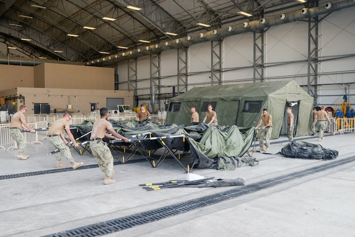 210819-N-IJ992-0183 U.S. 5TH FLEET AREA OF OPERATIONS (Aug. 19, 2021) - U.S. Navy personnel construct a tent in a hanger in the U.S. 5th Fleet area of operations for use during efforts to support the safe transit of U.S. citizens and evacuees from Afghanistan. The U.S. 5th Fleet area of operations encompasses nearly 2.5 million square miles of water area and includes the Arabian Gulf, Gulf of Oman, Red Sea and parts of the Indian Ocean. (U.S. Navy photo by Mass Communication Specialist Seaman Andy A. Anderson)