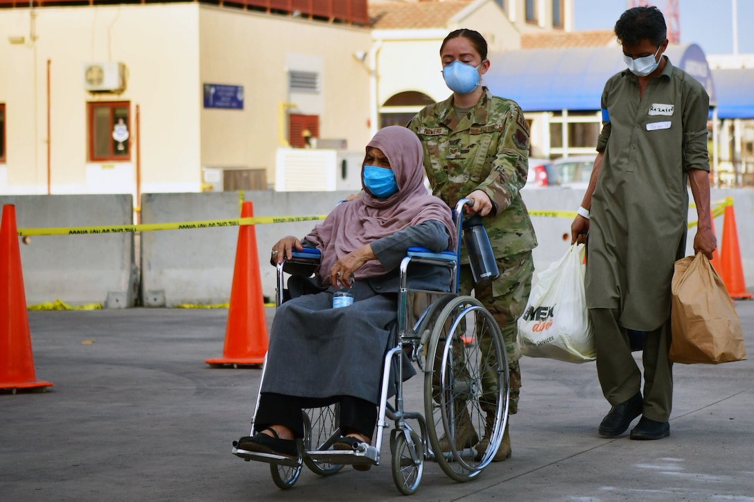 An airman pushes a person in a wheelchair while another follows holding bags.