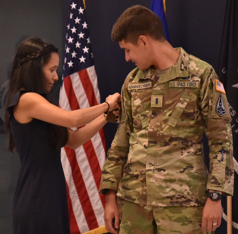 Capt. Cristian Hernández-Rivera's wife, Joanne Ortiz Merced, places his new Space Force insignia on his sleeve. (U.S. Air Force photo/Spencer Deer)
