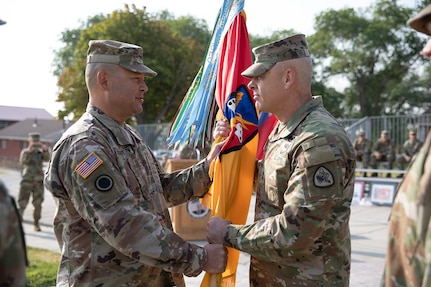 Maj. Gen. Michael Turley, the adjutant general, Utah National Guard, passes the organizational colors to the outgoing commander, Col. Steven A. Fairbourn, during the 65th Field Artillery Brigade change-of-command ceremony Aug. 8, 2021, at Camp Williams, Utah.