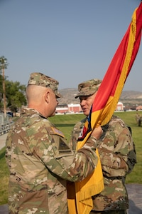 Col. Shawn M. Fuellenbach, the incoming commander of the 65th Field Artillery Brigade passes the organizational colors to Maj. Gen. Michael Turley, the adjutant general, Utah National Guard, during a change-of-command ceremony Aug. 8, 2021, at Camp Williams, Utah.