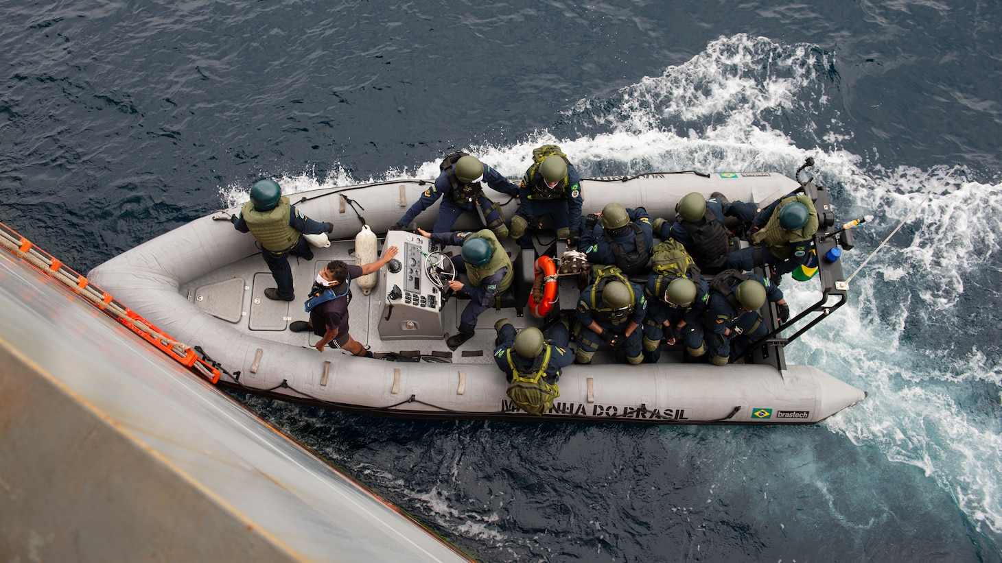 """Members of a Brazilian Navy visit, board, search, and seizure (VBSS) team return to their boat following a drill aboard the Expeditionary Sea Base USS Hershel """"Woody"""" Williams (ESB 4), Aug. 22, 2021. Hershel """"Woody"""" Williams is conducting a maritime security capability exercise to build on its existing partnership with the Brazilian Navy and joint interoperability operations with allies and partners during a scheduled deployment in the U.S. Sixth Fleet area of operations in support of U.S. national interests and security in Europe and Africa."""