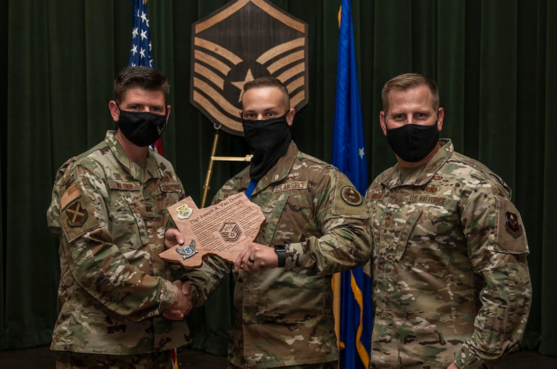 3 military members in front of a master sergeant plaque