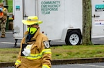 """An emergency responder in a reflective yellow coat stands in the foreground in a parking lot with a trailer in the background labeled """"Community Emergency Response Team."""""""