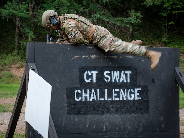 Tech. Sgt. Leo Otero, 103rd Security Forces Squadron, climbs over a wall during the Connecticut SWAT Challenge in East Granby, Connecticut, Aug. 18, 2021. The competition brings together tactical operators from across the nation to train SWAT weapons tactics, movements, and physical fitness. (U.S. Air National Guard photo by Tech. Sgt. Steven Tucker)