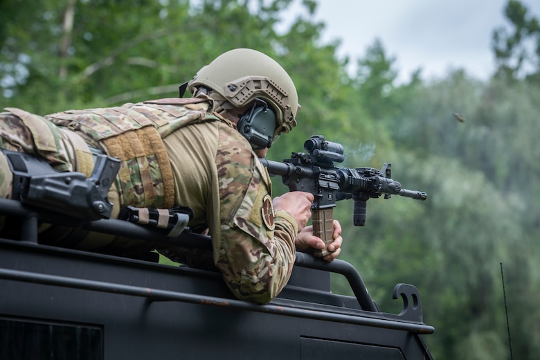 U.S. Air Force Staff Sgt. Adam Roach, 103rd Security Forces Squadron, fires an M4 carbine from the roof of a SWAT vehicle during the Connecticut SWAT Challenge in East Granby, Connecticut, Aug. 18, 2021. The competition brings together tactical operators from across the nation to train SWAT weapons tactics, movements, and physical fitness. (U.S. Air National Guard photo by Tech. Sgt. Steven Tucker)