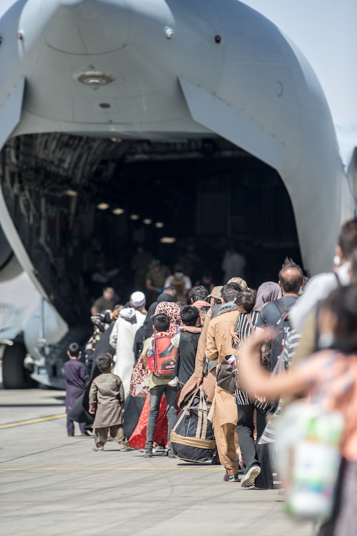 A long line of civilians enter the back of an aircraft.