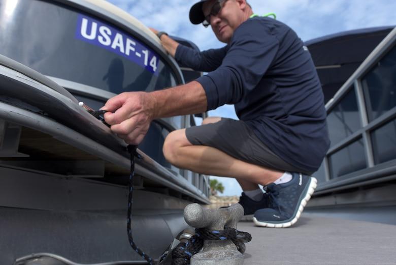 Man unties a docked boat