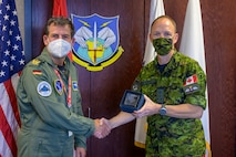 German Air Force Major-General Karsten Stoye, NATO's Chief of Staff Allied Air Command, exchanges gifts with Royal Canadian Air Force Lieutenant-General Alain Pelletier, Deputy Commander, North American Aerospace Defense Command, during his visit to the NORAD and U.S. Northern Command Headquarters at Peterson Space Force Base, Colorado, Aug. 23, 2021. Stoye traveled to the headquarters to receive information on the Global Information Dominance Experiments and discuss with leadership how NORAD and USNORTHCOM and NATO can collaborate on missile defense.