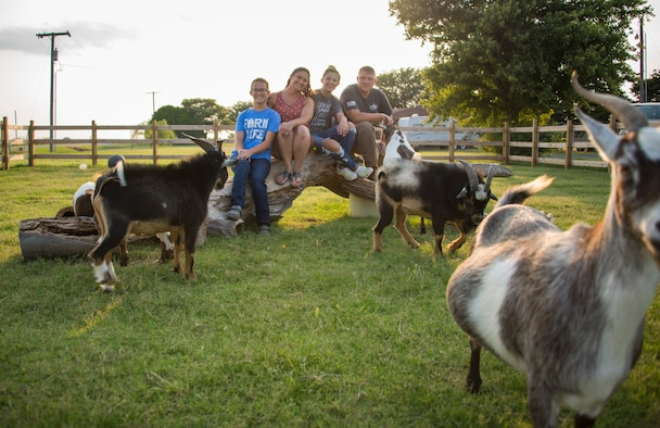 The Kessler family poses for a photo with their goats on 1AB Ranch in Altus, Oklahoma, Aug. 5, 2021. The family moved to their ranch in October of 2020 and have since amassed a number of goats, pigs, ducks, roosters and more. (U.S. Air Force photo by Senior Airman Amanda Lovelace)