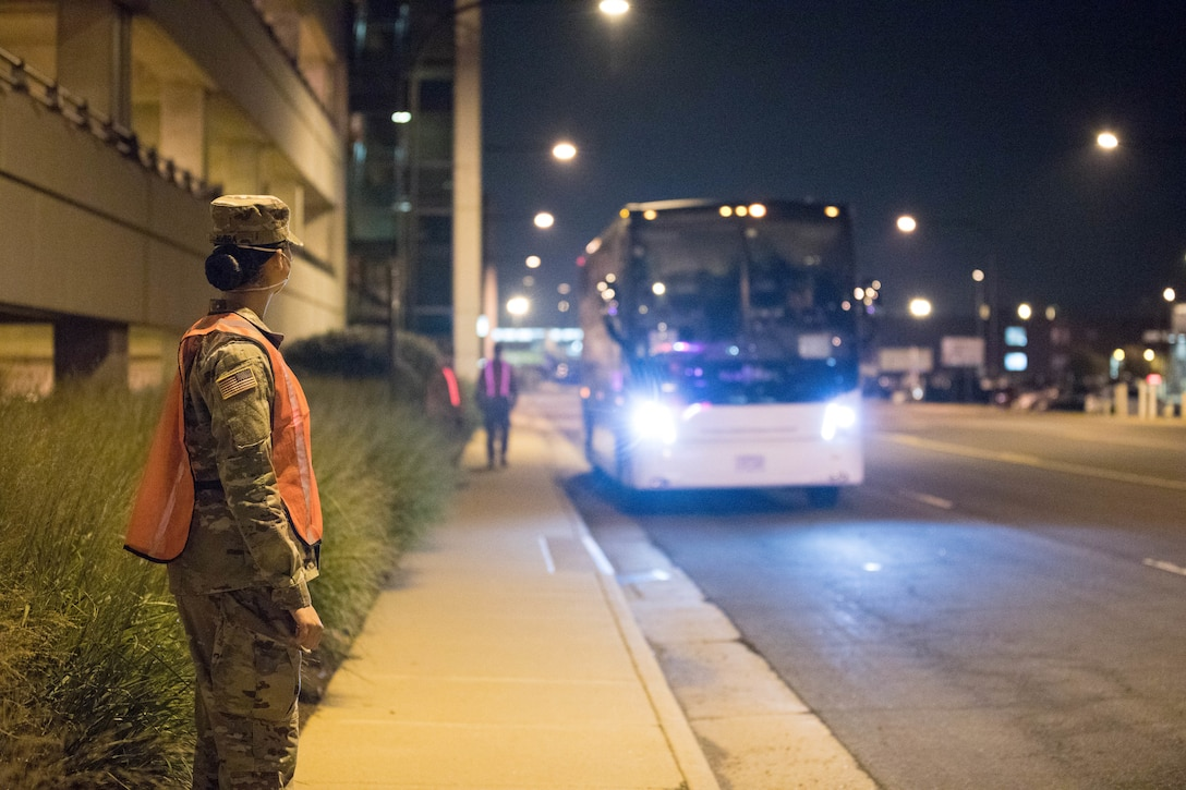U.S. Army Soldiers assigned to 804th Transportation Detachment, 382nd Combat Sustainment Support Battalion, help guide buses into position  in support of Operation Allies Refuge, July 29, 2021 at the Dulles International Airport in Virginia.