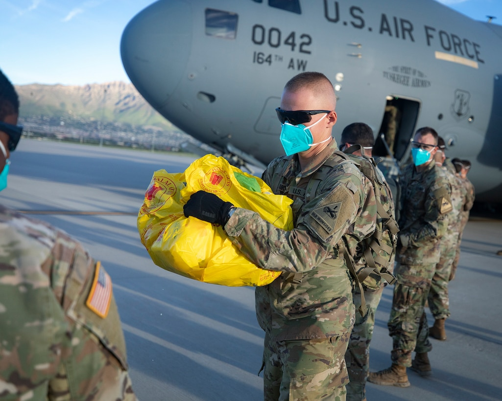 Soldiers from 2nd Armored Brigade Combat Team, 1st Armored Division assist as the first flight of Afghans arrive at Fort Bliss, Texas, Aug. 21, 2021.
