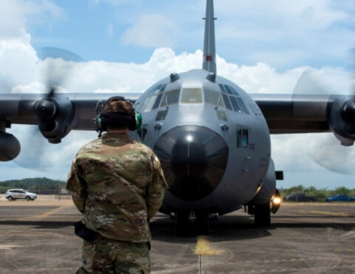 An Airman with the 123rd Contingency Response Group, Kentucky Air National Guard, waits to marshal a C-130 Hercules from the 133rd Airlift Wing in Aguadilla, Puerto Rico, Aug. 18, 2021. The Airman was part of a training exercise to respond to natural disasters and set up airbase operations.