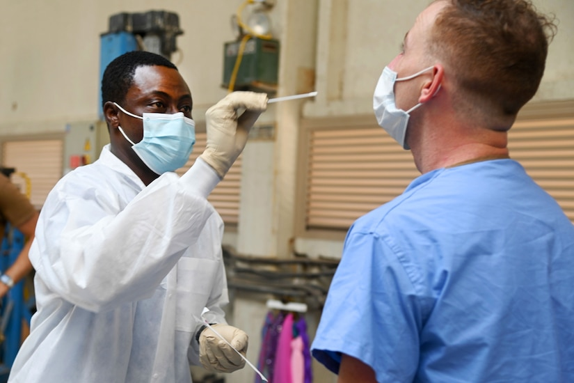 A man wearing a face mask and gloves holds a nasal swab while another man wearing a face mask tilts his head back.