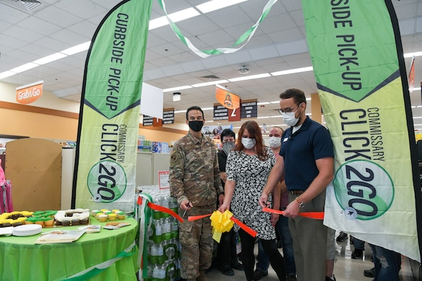 Col. Jeffrey Geraghty, left, commander of Arnold Engineering Development Complex headquartered at Arnold Air Force Base, Tenn., and Brandon Jelson, store director of the Arnold AFB Commissary, cut the ribbon during a ceremony to celebrate the launch of the CLICK2GO online ordering and curbside pick-up service at the commissary, Aug. 3, 2021. Also pictured, holding the ribbon, is Casey Cooper, grocery manager for the commissary. (U.S. Air Force photo by Jill Pickett)