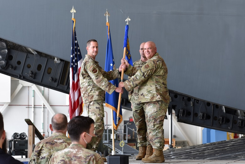 Col. John F. Robinson, 911th Airlift Wing commander, passes the 911th Maintenance Group guidon to Lt. Col. Richard Cox, 911th MXG commander, at the Pittsburgh International Airport Air Reserve Station, Pennsylvania, Aug. 8, 2021. The passing of the guidon symbolizes the transfer of command and that Cox assumes responsibility for the 911th Maintenance Group.