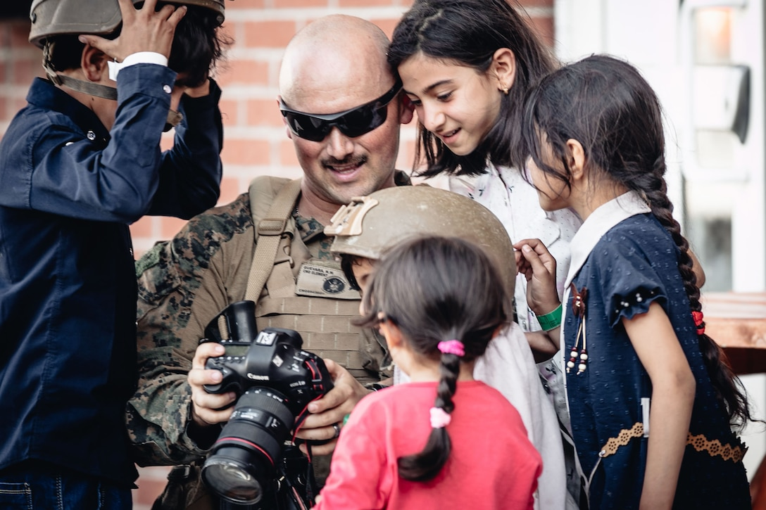 A Marine shows a camera to a group of smiling children.