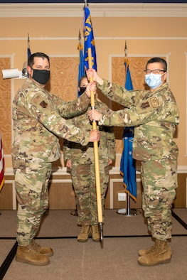 Col. Christopher G. Batterton, 192nd Wing commander, left, passes the 192nd Medical Group guidon to Col. Frank Y. Yang marking his assumption of command for the group.