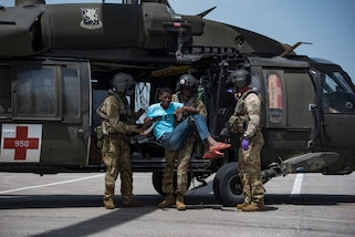 U.S. Soldiers with the 1st Battalion, 228th Aviation Regiment, Joint Task Force-Bravo, Soto Cano Air Base, Honduras, unload patients from a UH-60 Black Hawk helicopter during a medical evacuation mission in Port-au-Prince, Haiti, Aug. 24, 2021.