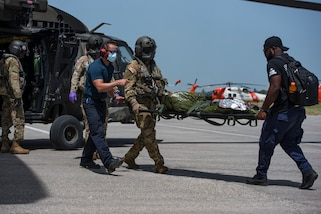 Medical volunteers and aircrew with the 1st Battalion, 228th Aviation Regiment, Joint Task Force-Bravo, Soto Cano Air Base, Honduras, unload patients from a UH-60 Black Hawk helicopter during a medical evacuation mission at Port-au-Prince, Haiti, Aug. 24, 2021.
