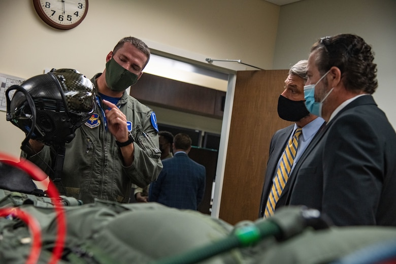 U.S. Air Force Capt. Daniel Henning, left, 62nd Fighter Squadron F-35A Lightning II instructor pilot, provides a helmet demonstration to Mark Brnovich, far right, Arizona Attorney General, Aug. 20, 2021, at Luke Air Force Base, Arizona. Brnovich received an aircrew flight equipment briefing paired with a hands-on AFE training during his visit. Brnovich toured the base and met with wing leadership to observe Luke's mission of training the world's greatest fighter pilots and combat-ready Airmen. (U.S. Air Force photo by Staff Sgt. Collette Brooks)