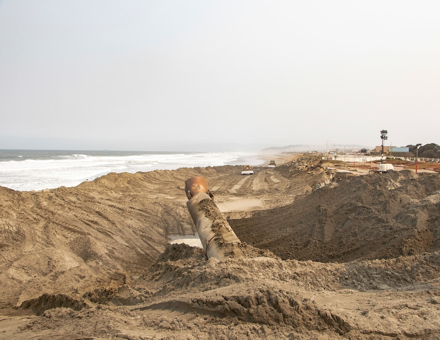 Beach front, ocean, sand being pumped ashore, construction equipment