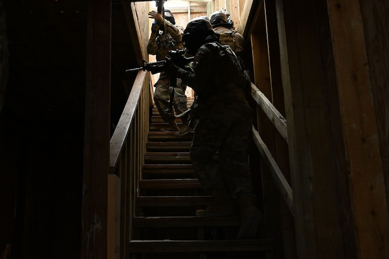 Defenders from the 841st Missile Security Forces Squadron navigate a dark staircase during a breaching exercise Aug. 17, 2021, at the firing range village on Fort Harrison, Mont. Simulated hostages and enemy combatants were inside the building, which required defenders to use critical weapon skills and decision-making while performing proper unit formations. (U.S. Air Force photo by Airman Elijah Van Zandt)