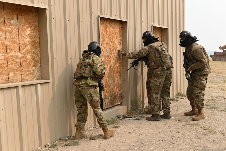 Defenders from the 841st Missile Security Forces Squadron prepare to breach a door Aug. 17, 2021, during a training exercise at the firing range village on Fort Harrison, Mont. The breach teams consisted of four defenders, who move through the building in specific formations to maximize vision and lethality. The training exercise is designed to teach defenders the proper technique of moving as a breaching unit, while simultaneously increasing confidence in stressful situations. (U.S. Air Force photo by Airman Elijah Van Zandt)