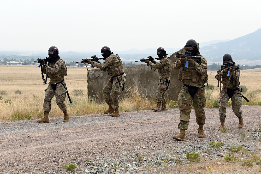 Defenders from the 841st Missile Security Forces Squadron patrol a village road in formation during a breaching exercise Aug. 17, 2021, at the firing range on Fort Harrison, Mont. The defenders' M4 carbines are armed with blue clips, which contain training ammunition to be used against simulated enemy combatants throughout the exercise. (U.S. Air Force photo by Airman Elijah Van Zandt)
